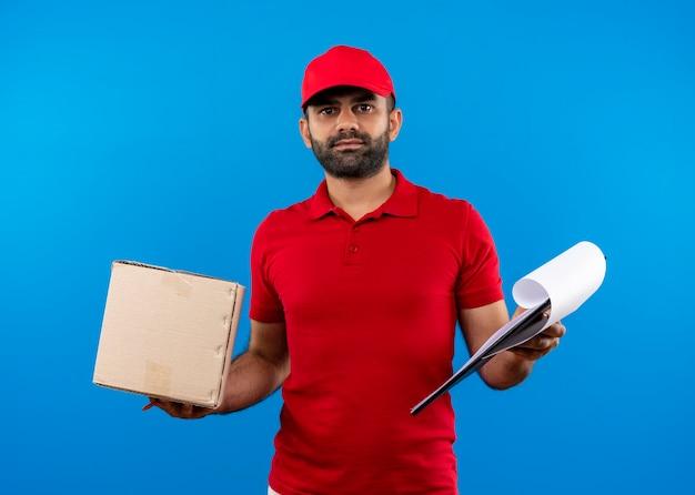 Bärtiger lieferbote in der roten uniform und in der kappe, die boxpaket und zwischenablage hält, die zuversichtlich stehen, über blauer wand zu stehen