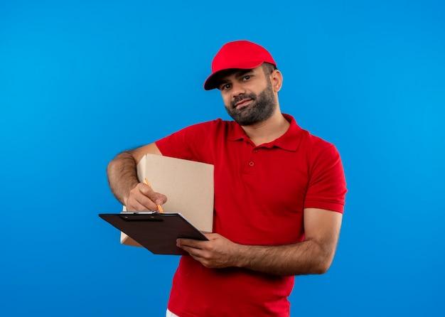Bärtiger lieferbote in der roten uniform und in der kappe, die boxpaket und zwischenablage hält, die zuversichtlich über der blauen wand stehen