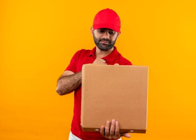Bärtiger lieferbote in der roten uniform und in der kappe, die die offene pizzaschachtel betrachtet, die es überrascht betrachtet, es mit ernstem gesicht betrachtend, das über orange wand steht