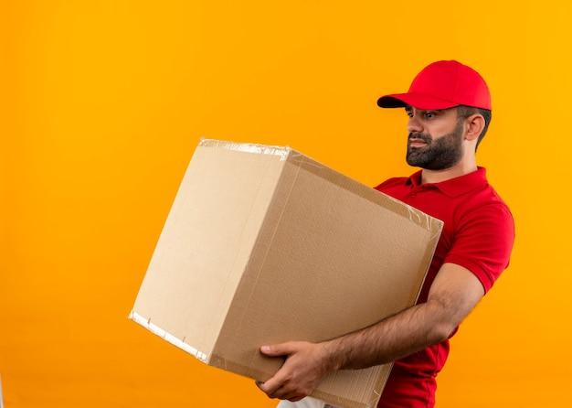 Bärtiger lieferbote in der roten uniform und in der kappe, die großes kastenpaket hält, das unter schwerem gewicht leidet, das über orange wand steht