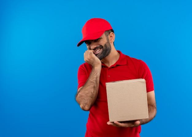 Bärtiger lieferbote in der roten uniform und in der kappe, die kastenpaket lächelnd glücklich und positiv steht über blauer wand