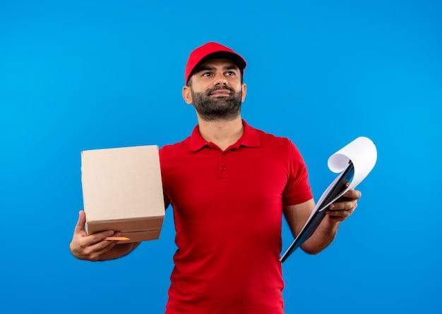 Bärtiger lieferbote in der roten uniform und in der kappe, die kastenpaket und zwischenablage hält lächelnd über der blauen wand stehend