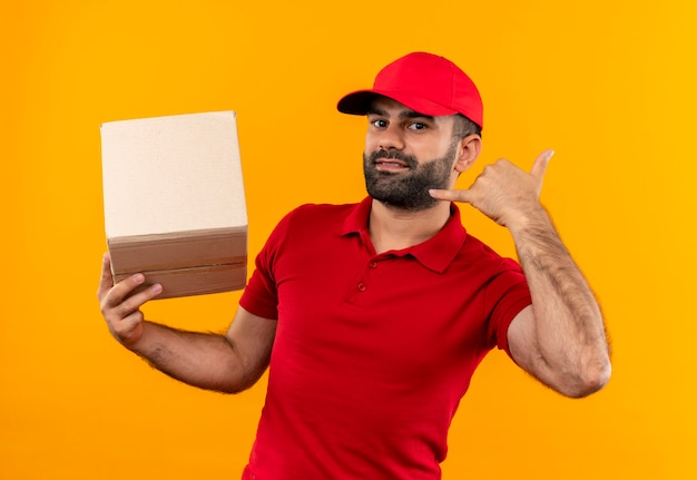 Bärtiger lieferbote in der roten uniform und in der kappe, die kastenverpackungspaket macht, rufen mich geste lächelnd an, die über orange wand steht
