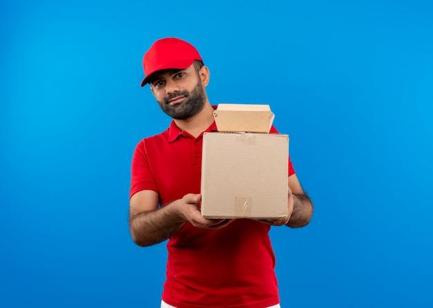 Bärtiger lieferbote in der roten uniform und in der kappe, die pappkartons halten, die mit lächeln auf gesicht stehen, das über blauer wand steht