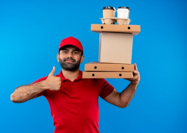 Bärtiger lieferbote in der roten uniform und in der kappe, die pappkartons mit lächeln auf gesicht hält, das daumen oben zeigt, die über blaue wand stehen