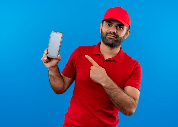 Bärtiger lieferbote in der roten uniform und in der kappe, die sein smartphone zeigt, das mit finger zeigt, der über blauer wand steht
