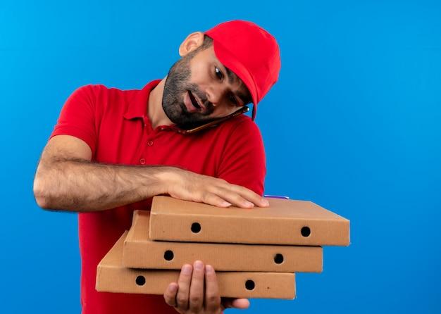 Bärtiger lieferbote in der roten uniform und in der kappe, die stapel von pizzaschachteln hält, die auf handy stehen, das über blauer wand steht