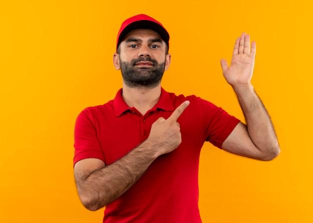 Bärtiger lieferbote in roter uniform und kappe, die mit finger zum arm zeigt, der über orange wand steht