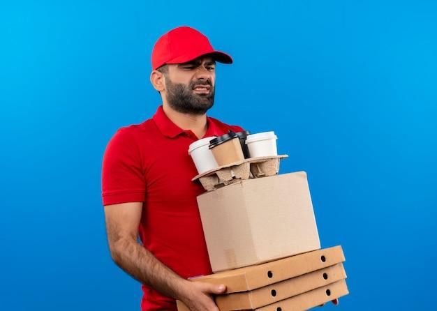 Bärtiger lieferbote in roter uniform und kappe, die pappkartons hält, die unzufrieden müde und überarbeitet über der blauen wand stehen