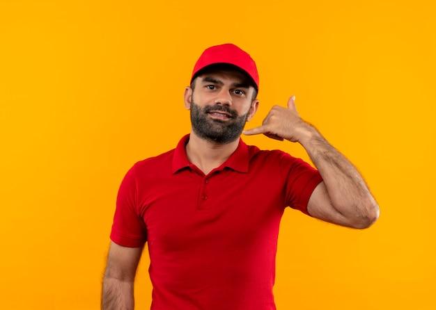 Bärtiger lieferbote in roter uniform und mütze, die zuversichtlich aussehen, rufen mich geste über orange wand