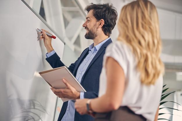 Bärtiger männlicher arbeiter, der auf whiteboard schreibt und lächelt, während er neben einer blonden frau steht