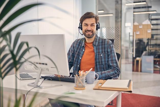 Bärtiger männlicher arbeiter im headset, der in die kamera schaut und lächelt, während er mit desktop-pc und notebook am tisch sitzt sitting