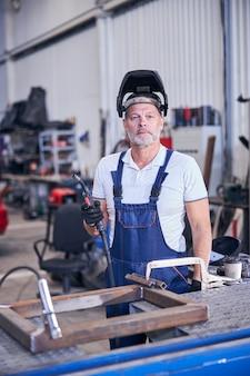 Bärtiger männlicher arbeiter mit schweißbrenner in der garage