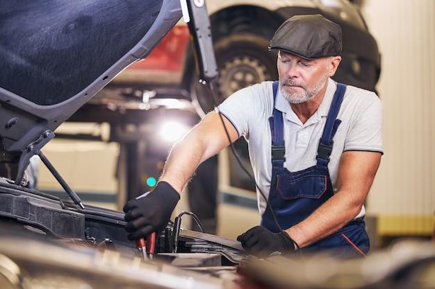 Bärtiger männlicher arbeiter repariert automotor an der tankstelle