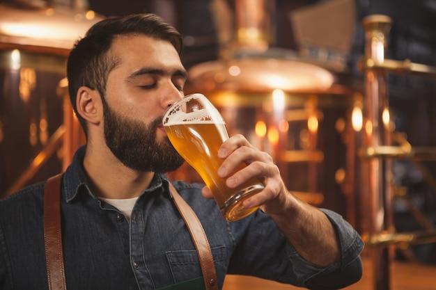 Bärtiger männlicher brauer, der köstliches bier aus einem glas nippt und in seiner produktionsbrauerei arbeitet