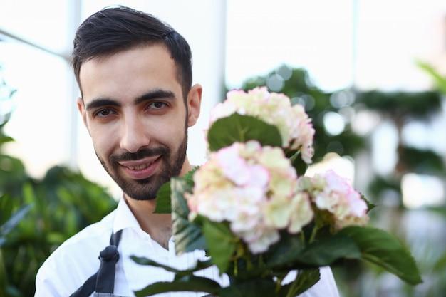 Bärtiger männlicher florist mit weißer blühender hortensie