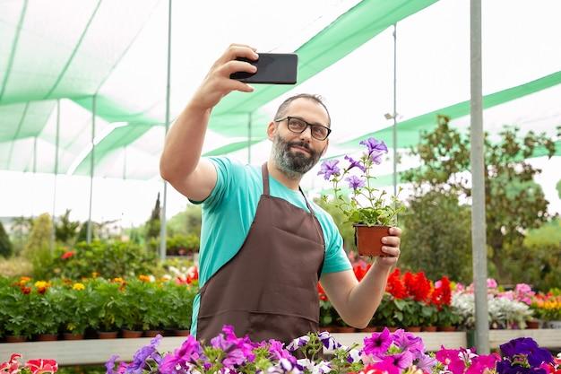 Bärtiger männlicher gärtner, der selfie mit eingetopfter petunie nimmt