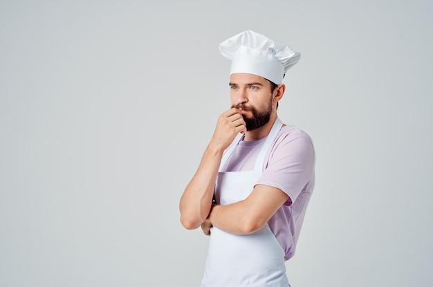 Bärtiger männlicher koch in restaurants mit küchengeschirr mit weißer schürze