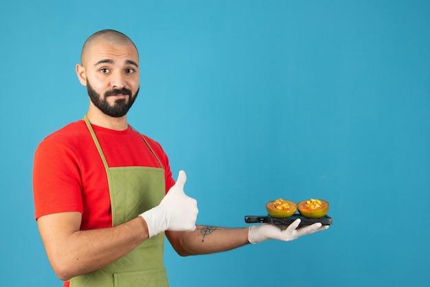 Bärtiger männlicher koch in schürze und handschuhen, der ein dunkles holzbrett mit gebäck hält.