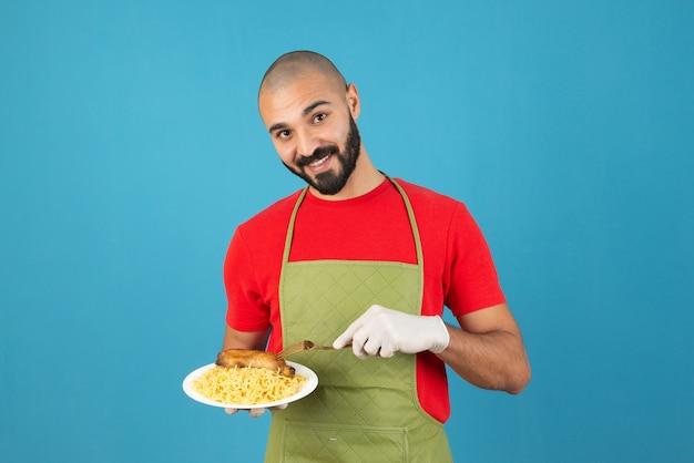 Bärtiger männlicher koch in schürze und handschuhen, der einen weißen teller mit köstlichen nudeln mit hühnerfleisch hält.
