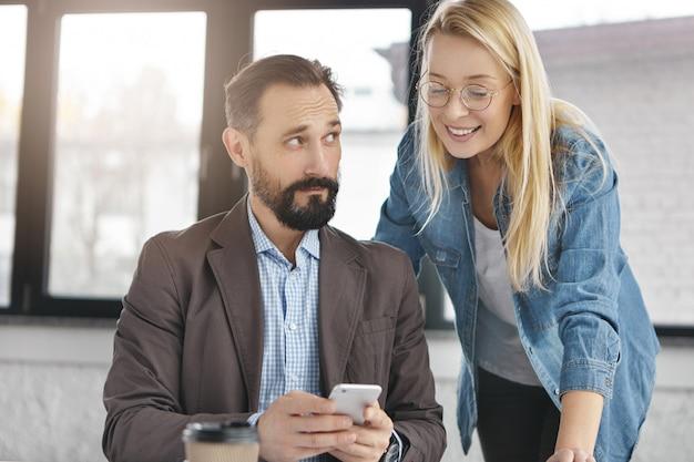 Bärtiger männlicher manager im formellen anzug und seine assistentin