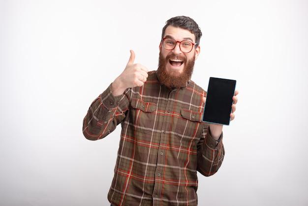 Bärtiger männlicher student zeigt wie geste und sein tablettbildschirm auf weißem hintergrund.