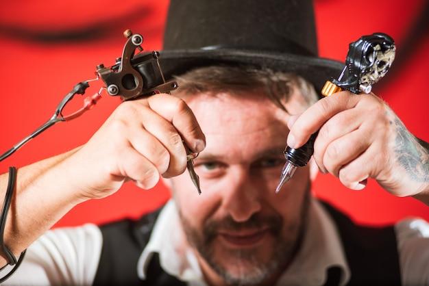 Bärtiger männlicher tätowierungsmeister mit tätowierungsmaschinengewehr in den händen