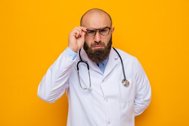 Bärtiger mann arzt im weißen kittel mit stethoskop um den hals, der kamera nah durch seine brille betrachtet, die über orange hintergrund steht