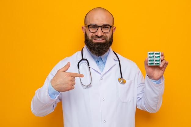 Bärtiger mann arzt im weißen kittel mit stethoskop um den hals trägt brille mit blase mit pillen, die mit dem zeigefinger darauf zeigen, fröhlich lächelnd