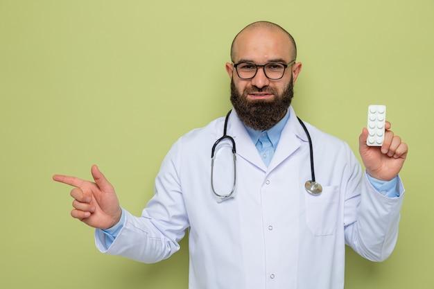 Bärtiger mann arzt im weißen kittel mit stethoskop um den hals tragen brille hält blase mit pillen glücklich und positiv mit zeigefinger zur seite lächelnd