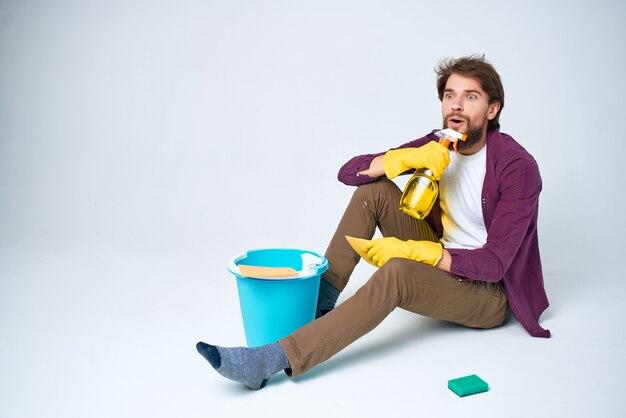 Bärtiger mann auf dem boden, der reinigungsmittel haushälter reinigt