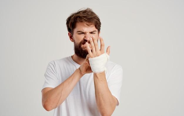 Bärtiger mann auf patient bandagierte handgesundheitsprobleme krankenhausmedizin