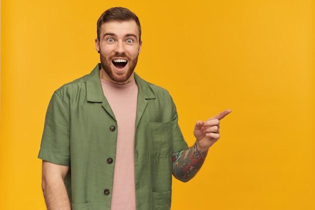Bärtiger mann, aufgeregter mann mit brünetten haaren. tragen einer grünen jacke mit kurzen ärmeln. hat tätowierung. und zeigefinger nach rechts auf den kopierbereich, isoliert über der gelben wand