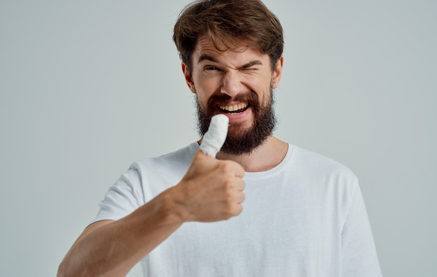 Bärtiger mann bandagierte daumengesundheitsproblemmedizin