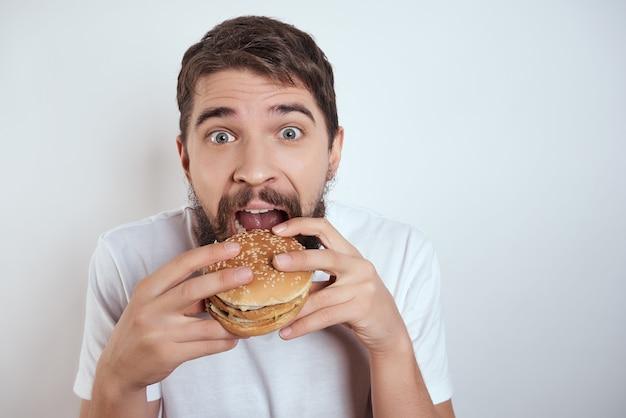 Bärtiger mann becher bier fast food verzerrt alkohol lebensstil. foto in hoher qualität