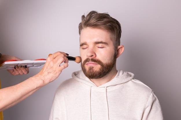 Bärtiger mann bekommt make-up-hand des visagisten mit pinsel