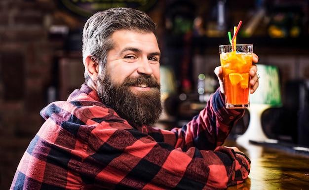Bärtiger mann-cocktail. porträtmann, orangensaft trinkend