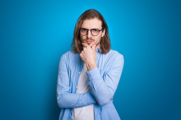 Bärtiger mann denkt auf blauem hintergrund schönheitsgesicht entscheidungsfindung
