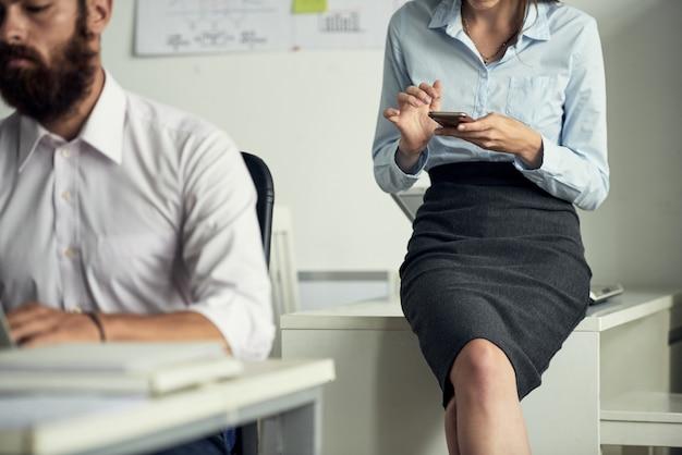Bärtiger mann, der am bürotisch sitzend arbeitet, während sein entspannter kollege texting messages on smartphone