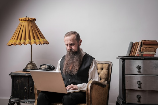 Bärtiger mann, der an einem laptop arbeitet