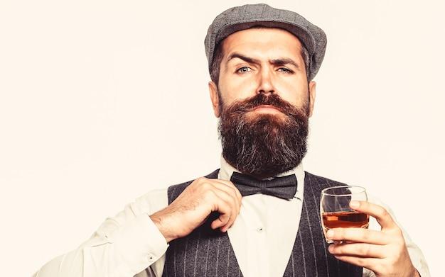 Bärtiger mann, der anzug trägt und whisky, brandy, cognac trinkt. eingebettet hält er ein glas whisky.