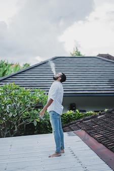 Bärtiger mann, der auf dem dach raucht