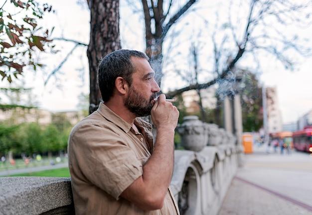 Bärtiger mann, der auf der straße raucht