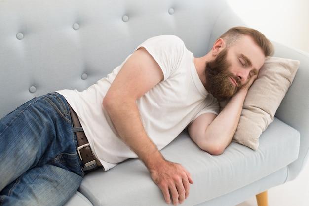 Bärtiger mann, der auf sofa liegt und dosiert