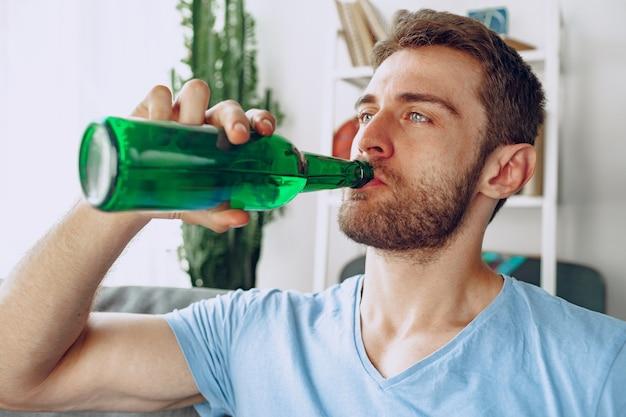 Bärtiger mann, der bier von der flasche trinkt, während zu hause auf sofa sitzen