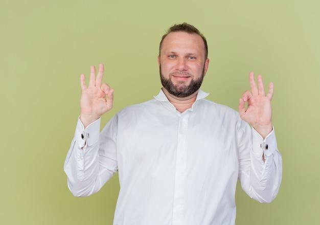 Bärtiger mann, der das lächelnde weiße hemd zeigt, das ok zeichen zeigt, das über lichtwand steht