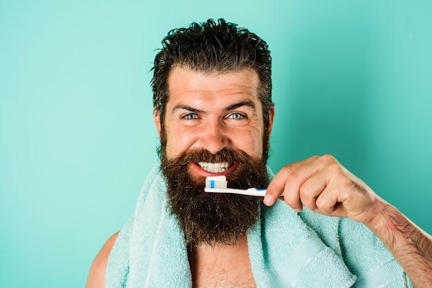 Bärtiger mann, der die zähne mit zahnbürste und zahnpasta putzt. zahnhygiene. behandlungen am morgen.