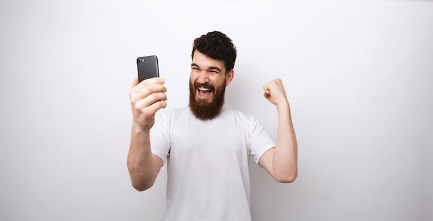 Bärtiger mann, der eine gewinnergeste macht und sein telefon auf weißem hintergrund betrachtet.