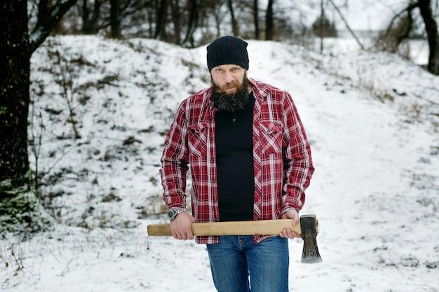 Bärtiger mann, der einen alten baum im winter im wald hackt