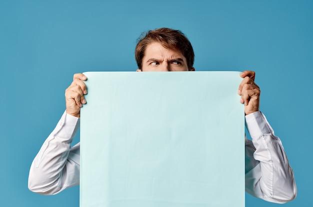 Bärtiger mann, der einen banner mit blauem hintergrund vor sich hält